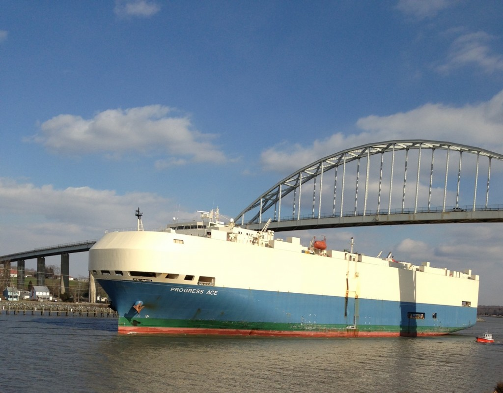 Big commercial ship going under the bridge on a sunny day