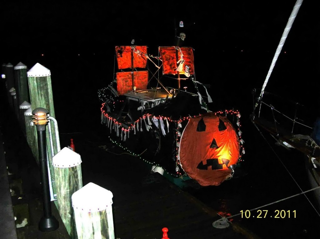 Night shot of a bot decorated for halloween with pumpkin and pirate masts