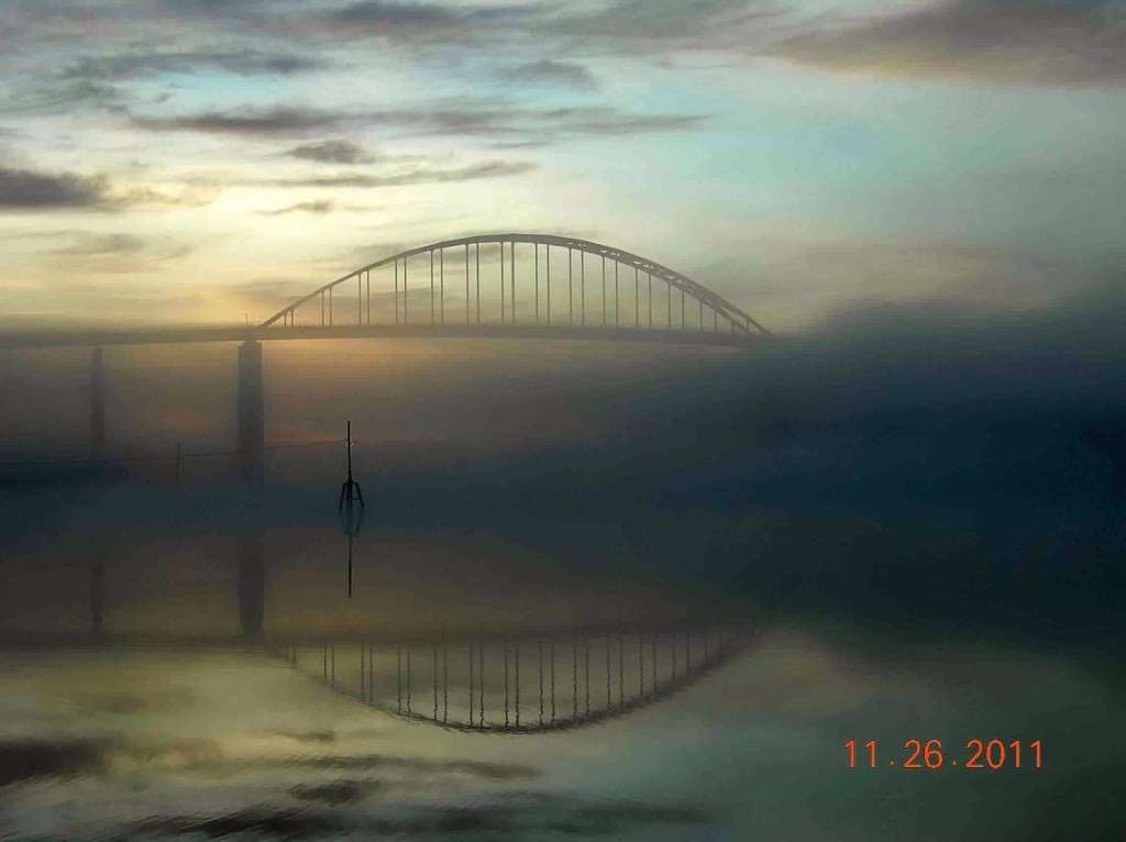 Bridge with a light in the wter and very heavy low fog and colorful sky