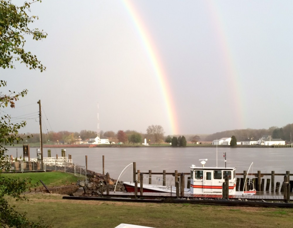 Double Rainbow over water with a tugboat in the foreground