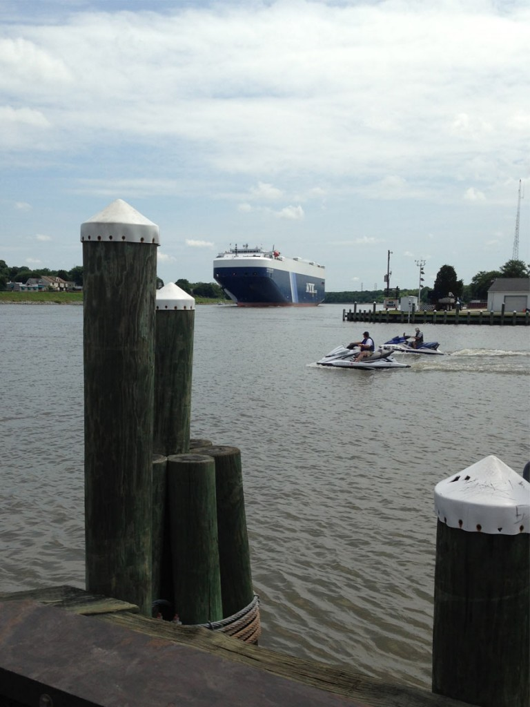 Photo from a dock with a commercial ship and jet skiers in water