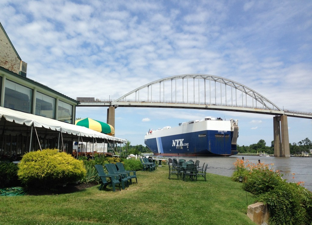 Freighter going under the bridge with Bayard House outdoor seating in foreground