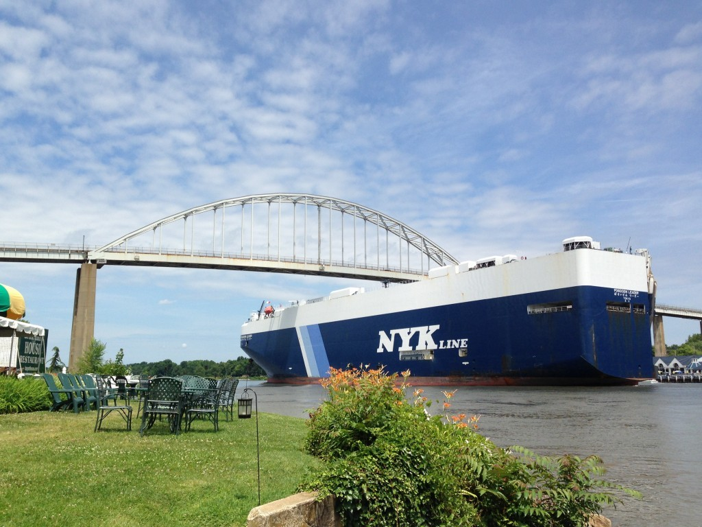 Large NYK Line commercial ship going under the bridge
