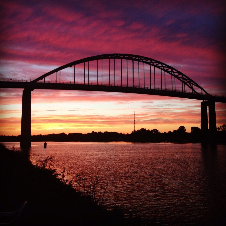 Colorful magenta sunset with bridge in silhouette