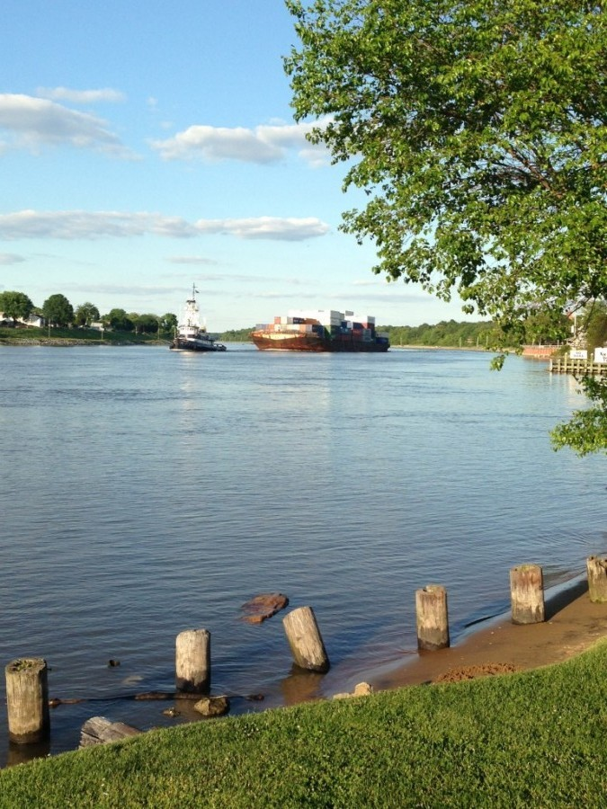 Tug boat towing cargo ship through the canal