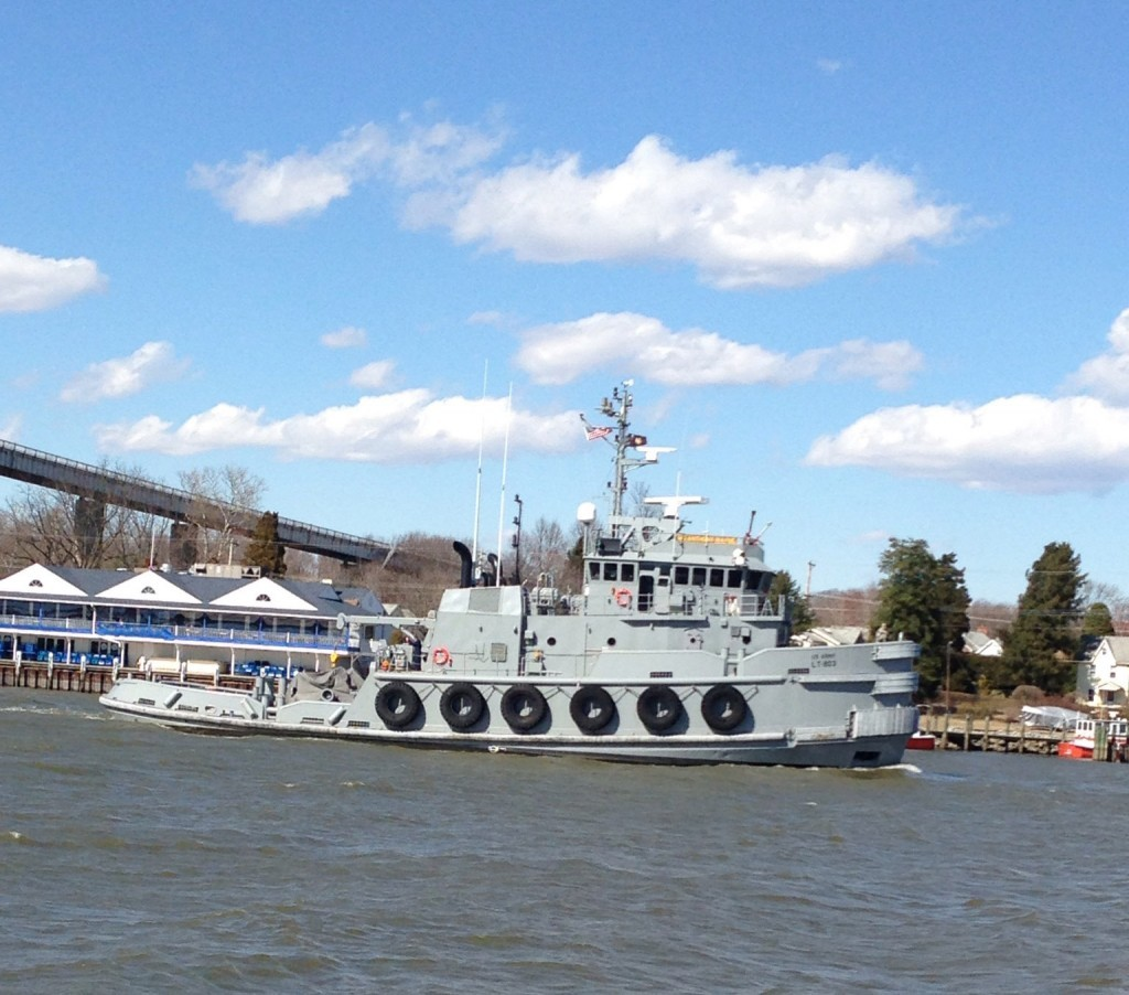 Gray coast guard boat with blue sky and puffy clouds
