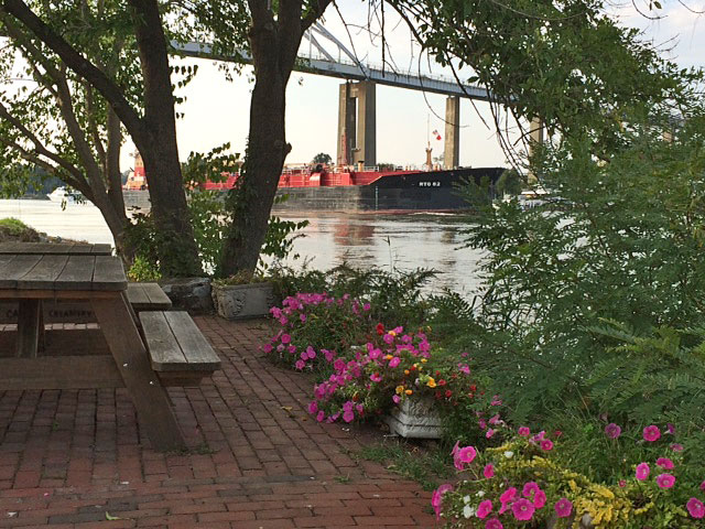 Brick paver area with picnic tables, tree and flowers next to water with freighter in distance