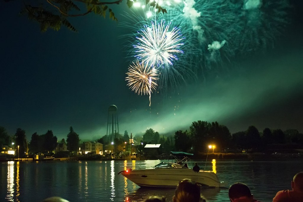 fireworks over the water with a boat in foreground