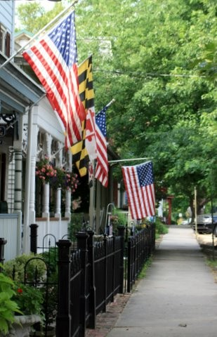 Flags flying from homes with black iron fences