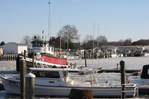 Tugboat and yacht in basic that is iced over