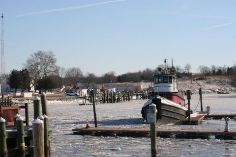 Docks and basic filled with ice with moored tugboat