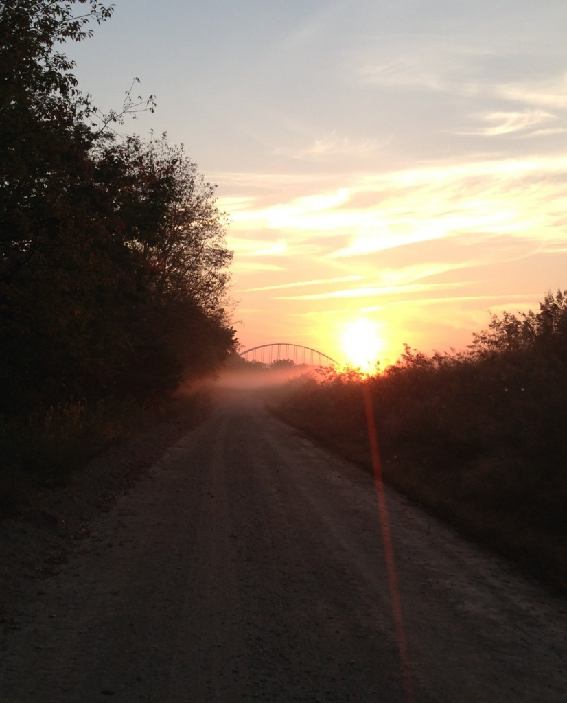 Sunrise with bridge from road near levees