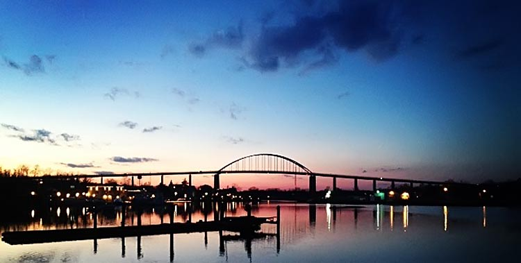 Sunset from across the basin with silhouettes of bridge and buildings