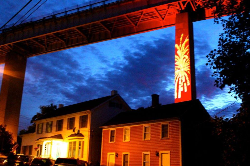 Colorful night scene of Chesapeake Bridge with firework design projected onto it