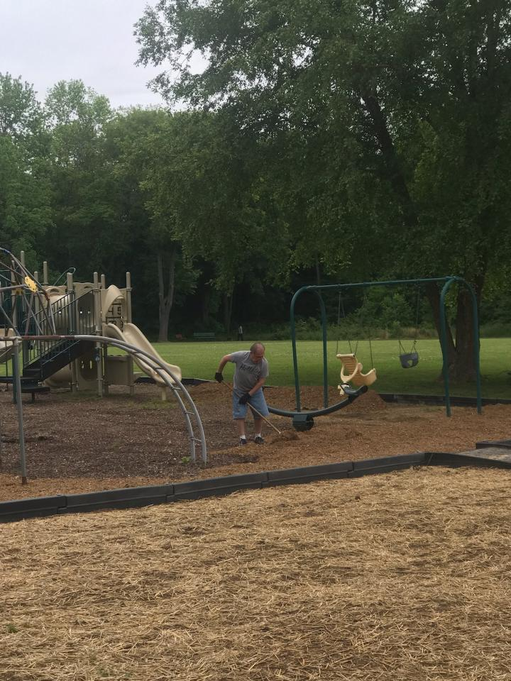 Outdoor playground with people on mulch